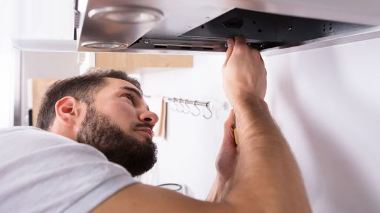 Repair man servicing kitchen vent